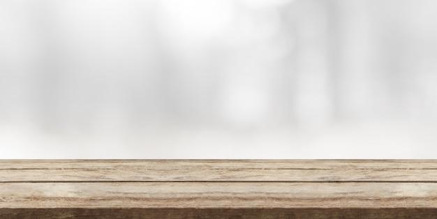 Hölzerne tischplatte vor abstraktem weißem bokeh hintergrund und kopienraum.