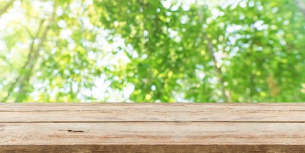 Hölzerne tischplatte vor natürlichem unschärfe bokeh hintergrund und kopienraum. produkte anzeigen oder montieren