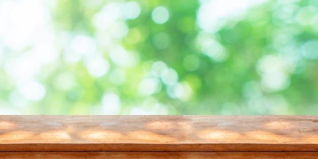 Hölzerne tischplatte vor natürlichem unschärfe bokeh hintergrund und kopienraum.