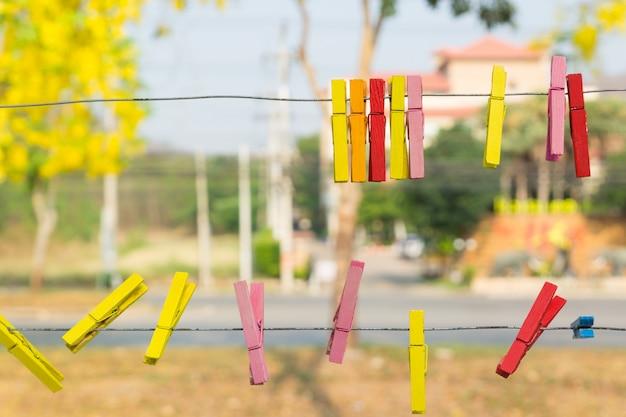 Hölzerne wäscheklammer, die am metalldraht hängt