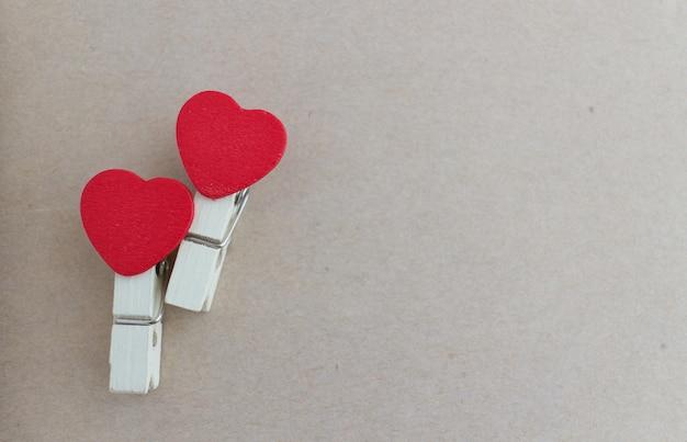 Hölzerne wäscheklammer mit herzformdesign und blatt des braunen papiers für valentinsgrußkonzept