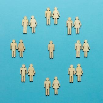 Hölzerne weibliche und männliche figuren paarweise und eine einsame silhouette.