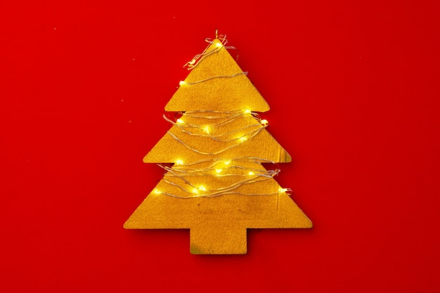 Hölzerne weihnachtsbaumdekoration mit lichtern auf rotem hintergrund draufsicht