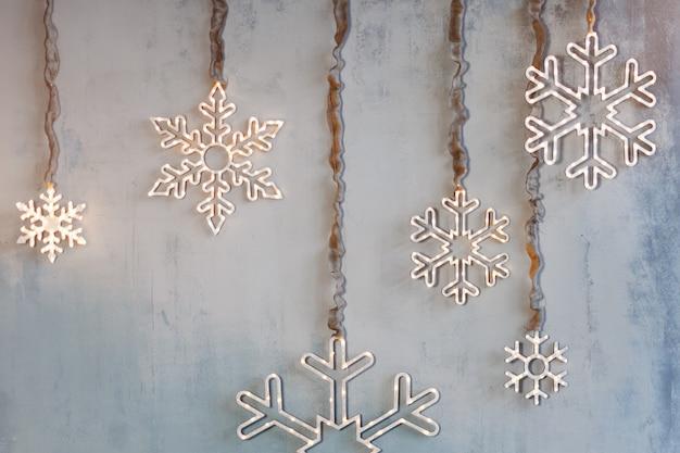 Hölzerne weihnachtsdekoration für die wände. glühende schneeflocken mit girlandenlichtern auf grauem betonhintergrund. weihnachtshintergrund, winterferienthema.