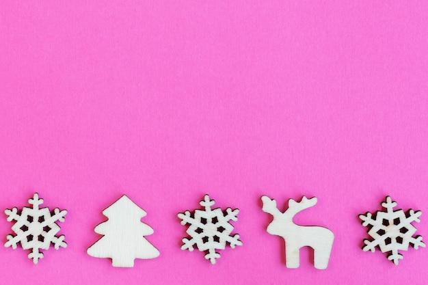 Hölzerne weihnachtsspielzeuge auf rosa hintergrund, draufsicht, flache lage, minimales neujahrskonzept, für design oder postkarte