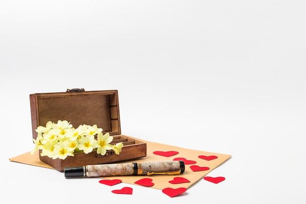 Hölzerne weinlese-schatulle, umschlag, stift, rote herzen der pappe und weiße frühlingsblumen auf einem weißen hintergrund.