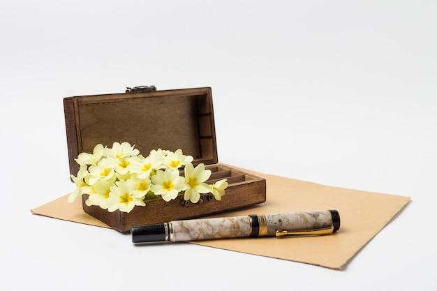 Hölzerne weinlese-schatulle, umschlag, stift und weiße frühlingsblumen auf einem weißen hintergrund