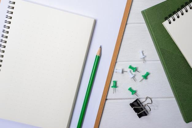 Hölzerne weiße schreibtischtabelle mit tasse kaffee, notizbuch, stift auf ihm.