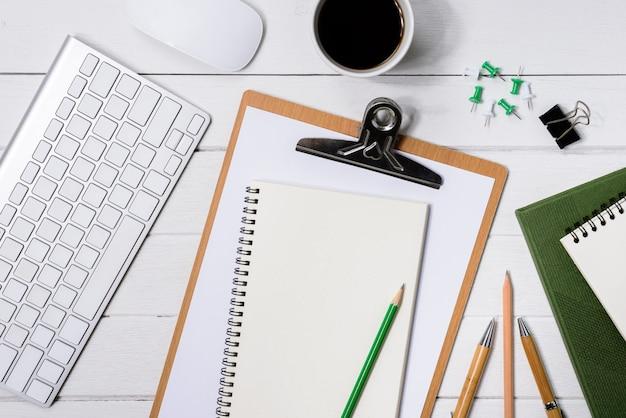 Hölzerne weiße schreibtischtabelle mit tasse kaffee, notizbuch, stift, auf ihm.
