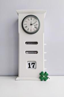 Hölzerne weiße vintage uhr mit kalender und kleeblatt auf grauem hintergrund. konzept des st. patrick's day save date zum feiern