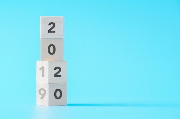 Hölzerne würfel, die vom konzept des neuen jahres 2019 bis 2020 auf getrenntem hintergrund mit exemplarplatz ändern