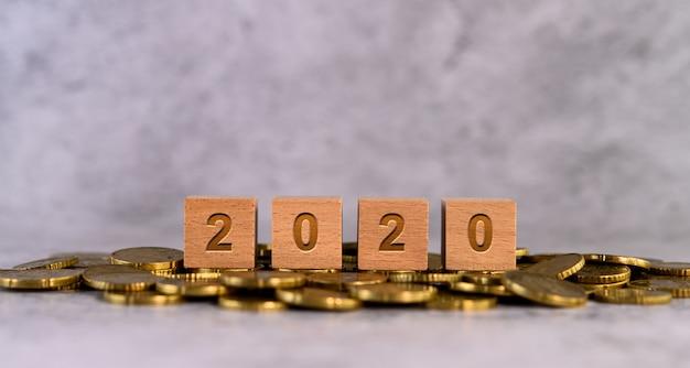 Hölzerne würfelbuchstaben des alphabetes mit 2020 wörtern gesetzt auf eine goldmünze
