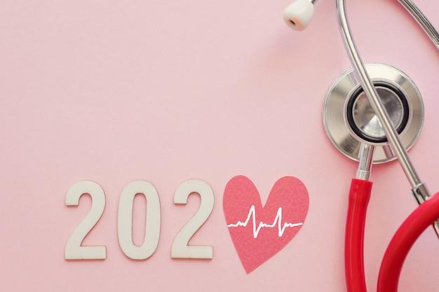 Hölzerne zahl 2020 mit rotem herzen und stethoskop auf rosa hintergrund
