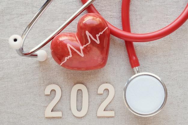 Hölzerne zahl 2020 mit rotem stethoskop. frohes neues jahr für herzgesundheit und medizin, lebensversicherungsgeschäft