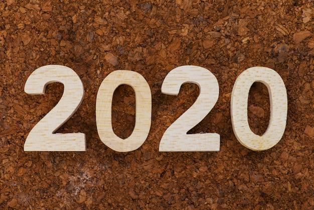 Hölzerne zahl von 2020 auf hölzernem abstraktem beschaffenheitshintergrund