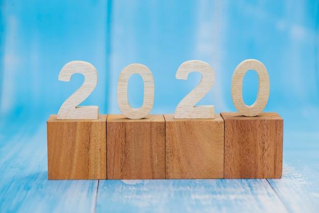Hölzerne zahl von 2020 mit leerem hölzernem würfelblock