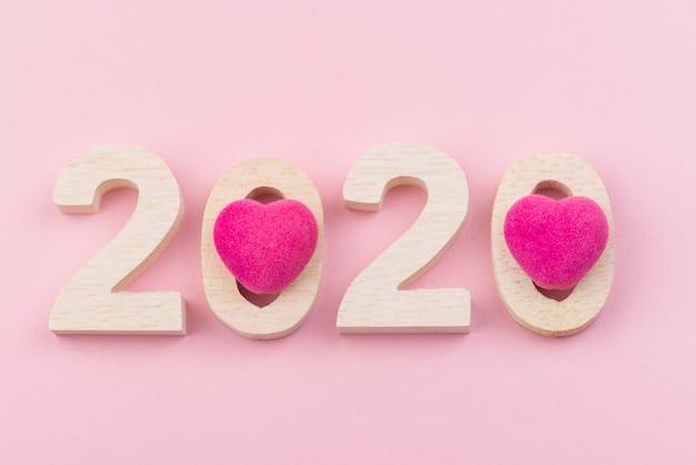 Hölzerne zahl von 2020 mit rosa herzen auf rosa hintergrund