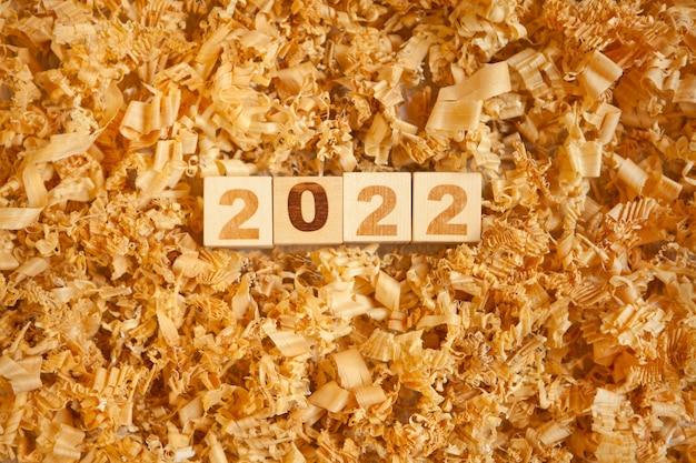 Hölzerne zahlen 2022 würfel symbolisieren weihnachten oder neujahrsfeier. spielzeug und holzspäne