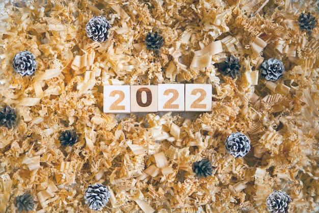 Hölzerne zahlenwürfel, die weihnachten oder neujahrsfeier tannenzapfen und späne symbolisieren
