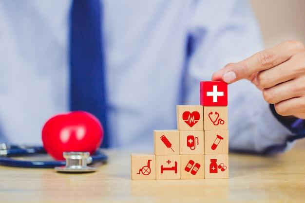 Hölzerner block der krankenversicherung, der mit dem ikonengesundheitswesen medizinisch stapelt.