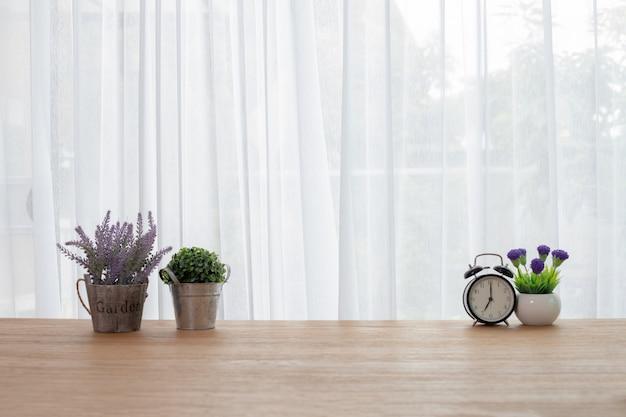 Hölzerner bürotisch mit blume auf weißem vorhanghintergrund.