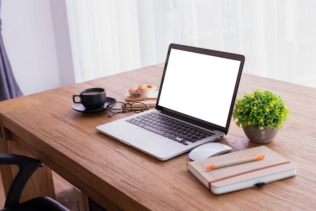 Hölzerner bürotisch mit leerem bildschirm auf laptop zu hause, kopienraum, spitzentabelle.