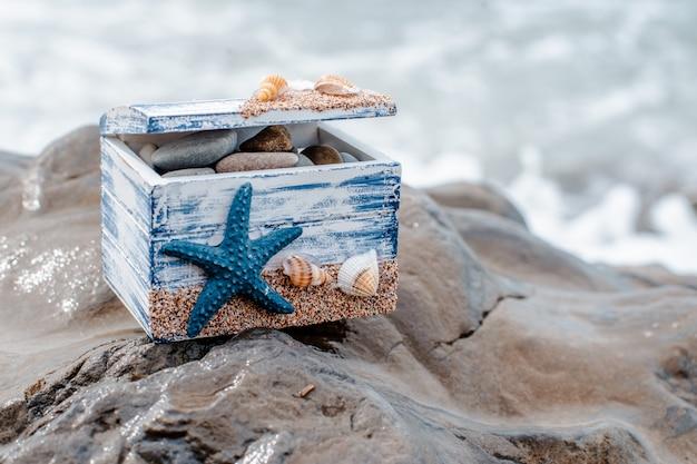 Hölzerner dekorativer kasten mit muscheln und blauer stern auf der seeküste.