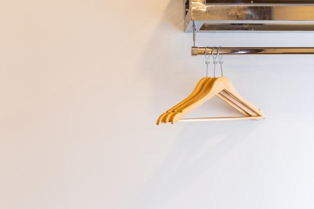 Hölzerner drei luxuskleiderbügel auf backsteinmauer nach innen