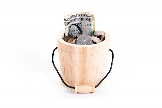 Hölzerner eimer und geld, us-dollars banknoten, penny, nickel, groschen, viertel