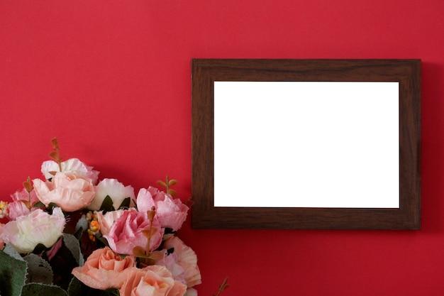 Hölzerner fotorahmen des modells mit raum für text oder bild auf rotem hintergrund und blume.