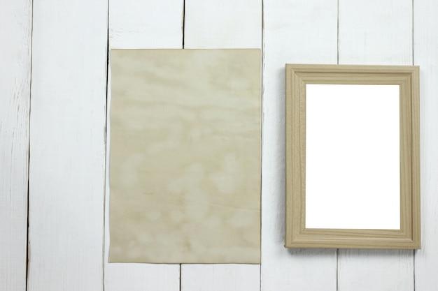 Hölzerner fotorahmen und altes leeres weinlesepapier auf weißem bretterboden.