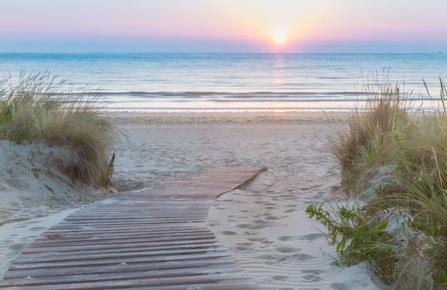 Hölzerner gehweg, der den strand bei sonnenaufgang betritt