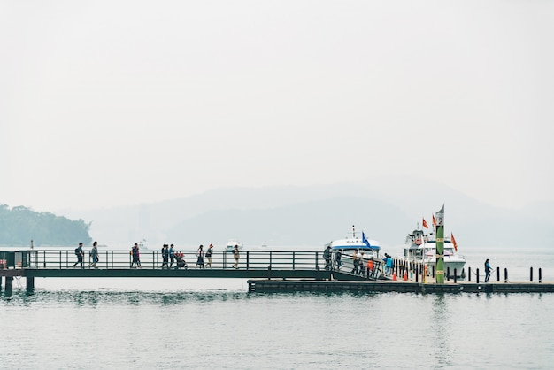 Hölzerner gehweg die führung zum boot in sun moon lake mit berg und wolke im hintergrund bei shuishe pier in yuchi-gemeinde, nantou county, taiwan.