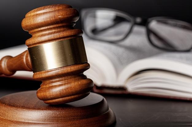 Hölzerner hammer und juristische bücher schließen oben