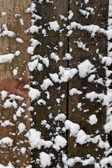Hölzerner hintergrund bedeckt mit schnee