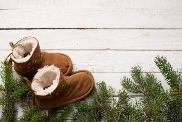 Hölzerner hintergrund des babywinters mit weihnachtsbaum und stiefel