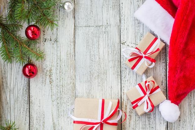 Hölzerner hintergrund des weihnachtsfeiertags mit tannenzweigen, sankt-hut und geschenkboxen