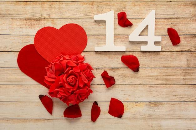 Hölzerner hintergrund mit blütenblättern, blumen, herzen und hölzernen zahlen vom 14. februar. das konzept des valentinstags.