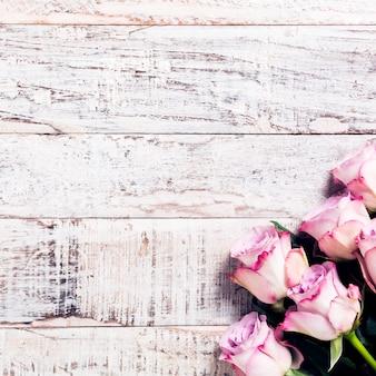 Hölzerner hintergrund mit blumenstrauß von rosa rosen