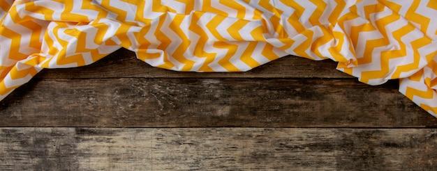 Hölzerner hintergrund mit einer gelben serviette. banner.