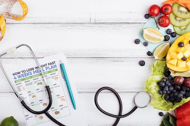 Hölzerner hintergrund mit frucht und stethoskop