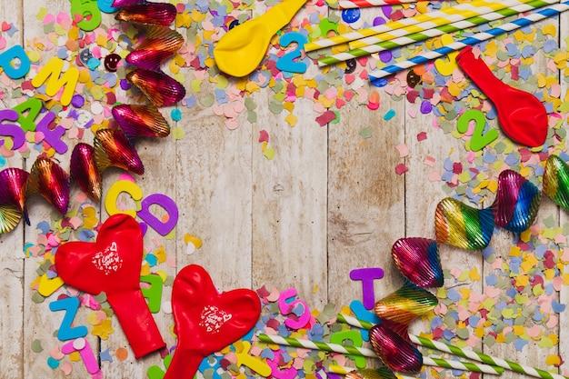 Hölzerner hintergrund mit konfetti und streamer um