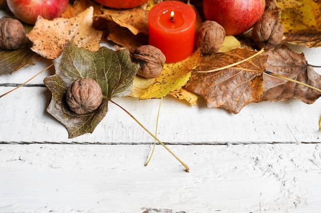 Hölzerner hintergrund mit nüssen, äpfeln, blättern, kerze