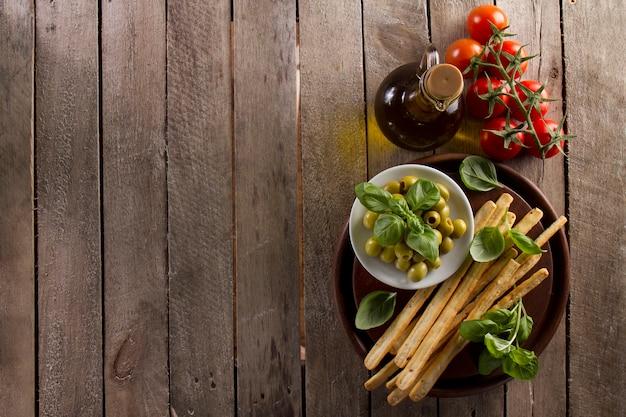 Hölzerner hintergrund mit olivenöl, tomaten und oliven