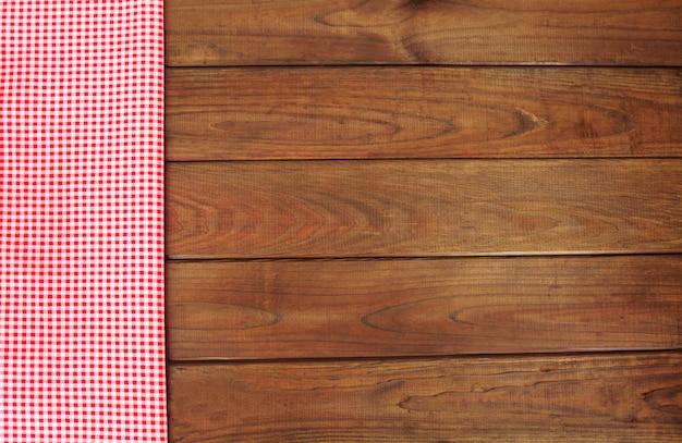 Hölzerner hintergrund mit roter und weißer karierter gewebegrenze.
