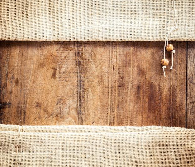 Hölzerner hintergrund mit sackleinenbeutel