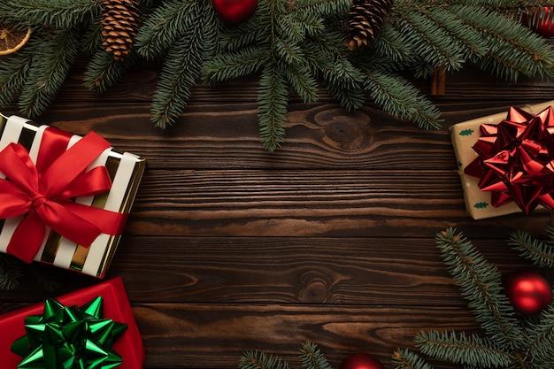 Hölzerner hintergrund verziert mit weihnachtsdekorationen und geschenken.