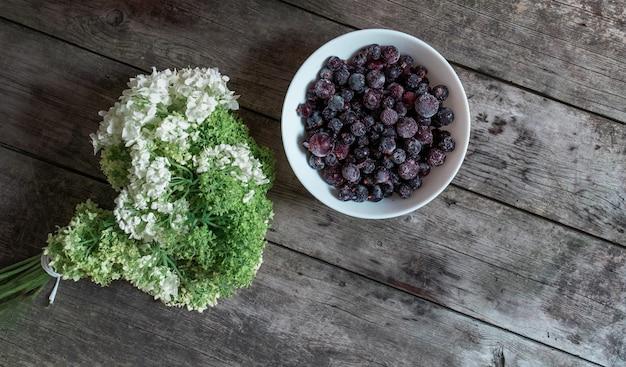 Hölzerner hintergrund von gray boards mit weißen und grünen blüten von hortensie und beeren.