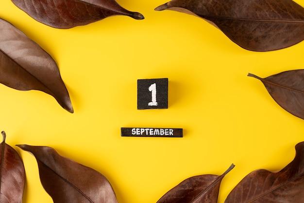 Hölzerner kalender 1. september und trockenes herbstlaub auf gelbem hintergrund draufsicht flach legen