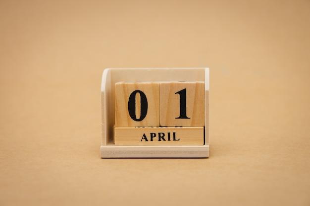 Hölzerner kalender am 1. april auf hölzernem abstraktem hintergrund der weinlese. erster april